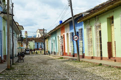 Colorful street in Trinidad (Cuba). Typical street in Trinidad (Cuba), with coloured houses and Saint Francis church and unidentified people as a background Royalty Free Stock Photography