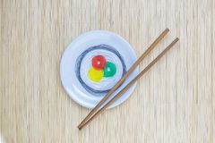 Colorful strings in form of sushi on white plate and sticks isolated on beige bamboo straw mat background. Sushi roll made of colorful threads on plate with Stock Image