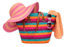 Colorful striped beach bag with a straw hat towel and sunglasses Stock Photos