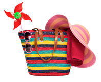 Colorful striped beach bag with a straw hat towel sunglasses and. A windmill toy, isolated on white Royalty Free Stock Image