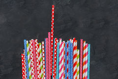Colorful striped cocktail straws on blackboard texture surface, abstract background Stock Image