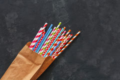 Colorful striped cocktail straws in craft package on blackboard background Royalty Free Stock Photos