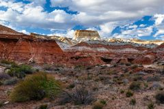 Colorful striped hills of southern Utah Badlands. Colorfully striped hills of the southern Utah badlands with bright blue sky and white clouds in the background royalty free stock image