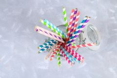 Colorful striped paper disposable tubes in a jar on a gray background. Colorful striped paper disposable tubes in a jar on a gray background Royalty Free Stock Photos