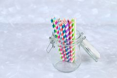 Colorful striped paper disposable tubes in a jar on a gray background. Colorful striped paper disposable tubes in a jar on a gray background Royalty Free Stock Images