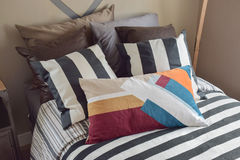 Colorful striped pillow on black striped bedding in light brown Stock Photography