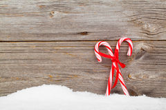 Colorful striped red and white Xmas candy canes with winter snow. On wooden boards, with copyspace stock photography