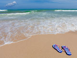 Colorful striped sandals on sea beach Royalty Free Stock Photos