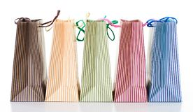 Colorful striped shopping bags arranged in a row, object isolated on white royalty free stock images