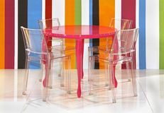Colorful stripes. Transparent plastic chairs inside colorful interior with stripes wall Royalty Free Stock Photos