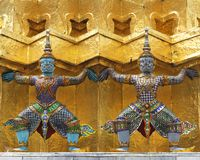 Figures of giants carrying golden chedi Stock Images