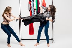 Colorful studio image of two beautiful young women standing, holding jacket, fighting over it