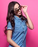Colorful studio portrait of a young woman surprised looking at something over sunglasses. Beautiful dark wavy hair, a denim shirt. Pink background Royalty Free Stock Images