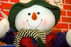 Colorful stuffed snowman. A colorfully stuffed toy snowman with a carrot nose and all dressed up in winter clothing against a red brick background Stock Image
