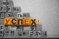 Colorful success word in Russian language. Among grey cubes with letters Royalty Free Stock Photo