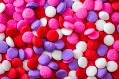 Colorful sugar sprinkles. Macro of a group of small edible sugar sprinkles in different hades of reds and white a valentines decorations background stock images