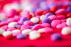 Colorful sugar sprinkles. Macro of a group of small edible sugar sprinkles in different hades of reds and white a valentines decorations background stock photo