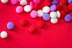 Colorful sugar sprinkles. Macro of a group of small edible sugar sprinkles in different hades of reds and white a valentines decorations fading into a red royalty free stock photography