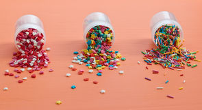 Colorful sugar sprinkles scattered on a wooden table Stock Photos