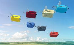 Suitcases gathered in a flock, like birds and flew on vacation. Colorful suitcases with small wings fly on vacation high above the ground like a flock of birds Royalty Free Stock Photo