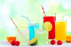 Colorful summer drinks with a green outdoors background. Group of colorful summer drinks against a green outdoors background Royalty Free Stock Photography