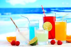 Colorful summer drinks with a vibrant blue ocean background. Group of colorful summer drinks against a vibrant blue ocean background Stock Photo