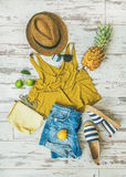 Colorful summer fashion outfit flat-lay over pastel background. Colorful summer fashion outfit flat-lay. Denim shorts, straw sun hat, yellow top, espadrillas Stock Photos