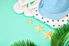Colorful summer female fashion outfit. Beach, vacation, travel concept. Summer female fashion outfit. Sunhat, white flip flops, polka dot towel, and starfish royalty free stock photos