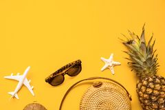 Colorful summer female fashion outfit flat lay. Straw bag, sunglasses, coconut, pineapple and air plane over yellow background. Top view. Summer travel holiday royalty free stock image
