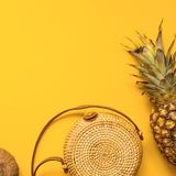 Colorful summer female fashion outfit flat lay. Straw hat, bamboo bag, sunglasses, coconut, pineapple over yellow background. Top view. Summer fashion, holiday royalty free stock images