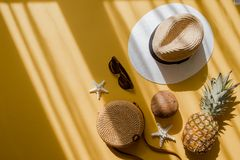 Colorful summer female fashion outfit flat lay. Straw hat, bamboo bag, sunglasses, coconut, pineapple over yellow background. Colorful summer female fashion stock image