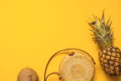 Colorful summer female fashion outfit flat lay. Straw hat, bamboo bag, sunglasses, coconut, pineapple over yellow background. Top view. Summer fashion, holiday stock photos