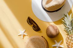 Colorful summer female fashion outfit flat lay. Straw hat, bamboo bag, sunglasses, coconut, pineapple over yellow background. Colorful summer female fashion royalty free stock photos