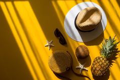 Straw hat, bamboo bag, sunglasses, coconut, pineapple, starfish over yellow background, top view. Colorful summer female fashion outfit flat lay. Straw hat royalty free stock photos