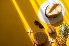 Colorful summer female fashion outfit flat lay. Straw hat, bamboo bag, sunglasses, coconut, pineapple, starfish over yellow. Background, top view. Summer royalty free stock photography