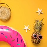 Colorful flat lay with pink inflatable circle donut, funny pineapple in sunglasses, bamboo bag and starfish over yellow background. Colorful summer flat lay with royalty free stock image