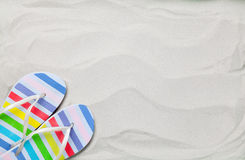 Colorful summer flip flops on white sand. Stock Images