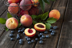 Colorful summer fruits - nectarines and peaches on wooden table Stock Photo
