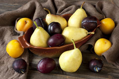 Colorful summer fruits -plums and pears on wooden table Stock Images