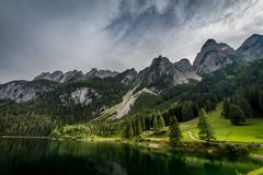 Colorful summer scene of side Vorderer Gosausee lake with forest and rocky hills at background in Austria royalty free stock images