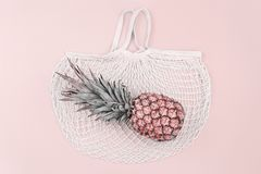 Summer shopping sale concept. Colorful summer shopping flat-lay. Ripe Pineapple over cotton mesh bag, top view, copy space. Summer shopping sale routine and stock photos