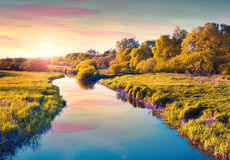 Colorful summer sunrise on the river. Stock Photos