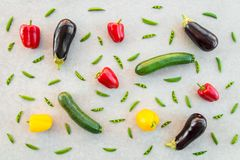 Colorful summer vegetables on concrete background. Red and yellow peppers, zucchini, eggplants, and green peas stock photography