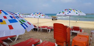 Colorful sun shadow umbrellas and orange chairs. On the beach near the sea royalty free stock photography