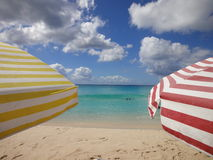 Colorful sun umbrellas on the beach. Two colorful sun umbrellas on a beautiful white sandy beach Mullet Bay in Sint Maarten, the Caribbean Royalty Free Stock Image