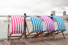 Colorful sunbeds at the beach with nice view to the sea. Colorful sunbeds on urban pier at the seaside with lovely view to the calm sea and city of Brighton Stock Photo