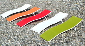Colorful sunbeds on a deserted pebble beach Royalty Free Stock Image