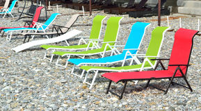 Colorful sunbeds  on a deserted pebble beach Stock Image