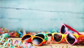 Colorful sunglasses and party streamers royalty free stock images
