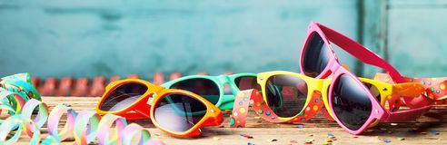 Colorful sunglasses and party streamers. Wide angled view of colorful sunglasses and party streamers, carnival themed background stock photography